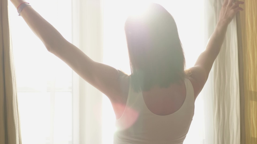 Lovely girl is awake and standing before window. Beautiful woman opening curtains and looking through the window. | Shutterstock HD Video #1034023253