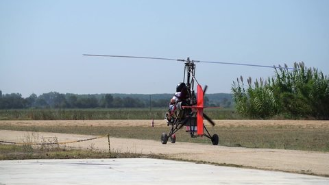 Ultralight gyrocopter autogyro with pilot picking up speed moving on unpaved runway before taking off