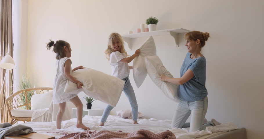 Happy family young mom and little cute children siblings playing pillow fight on bed, cheerful mother laughing having fun enjoying morning funny game with small active kids girls daughters in bedroom | Shutterstock HD Video #1034100983