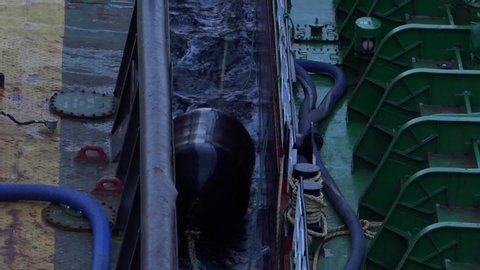 black huge safety barrel with long brown ropes floats between modern oil tankers on waving sea water closeup
