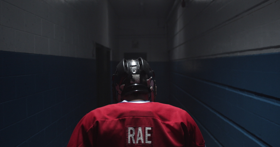 Following hockey player over the shoulder walking down a hallway with intensity towards hockey arena during the playoffs. | Shutterstock HD Video #1034196983