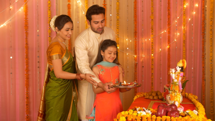 Indian Nuclear family worshiping Lord Krishna with Puja Thali - Love and care. Family bonding. Indian stock video of parents teaching Hindu customs and traditions to their little daughter