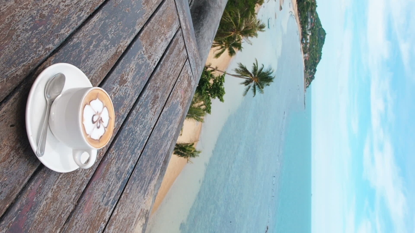 Vertical video footage. Flavored coffee in white cup on plate with spoon on wooden rustic table, sea background with the sea waves movement. Drinking coffee with a sea view at a tropical resort | Shutterstock HD Video #1034246993