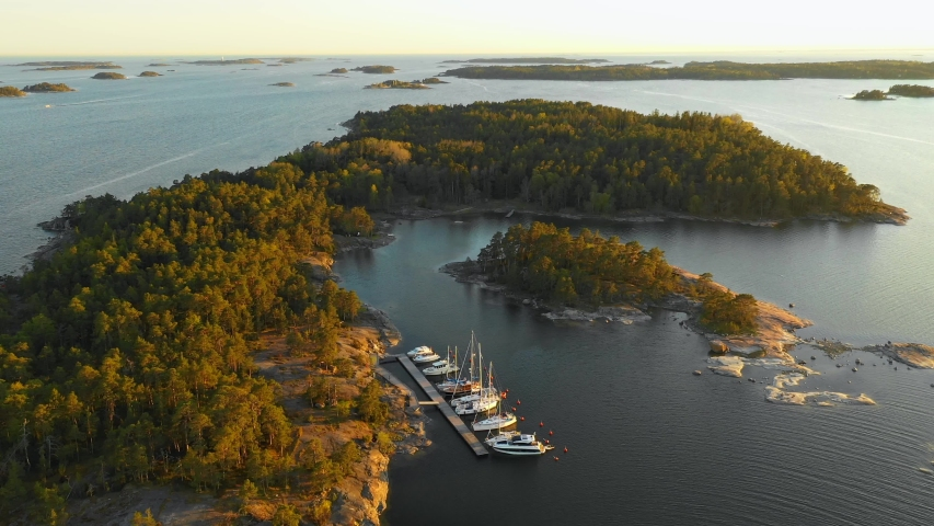 Aerial, reverse, drone shot, over a small harbor on Utterbote island, in the Finnish archipelago, at the Gulf of Finland, golden hour, on a summer evening, on the coast of Porkkala. in Uusimaa, Suomi | Shutterstock HD Video #1034282183