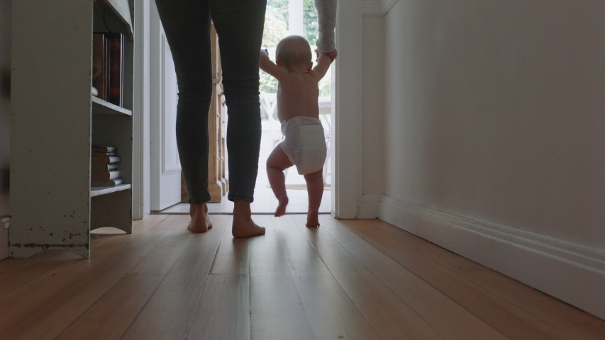 Baby learning to walk toddler taking first steps with mother helping infant teaching child at home | Shutterstock HD Video #1034286623