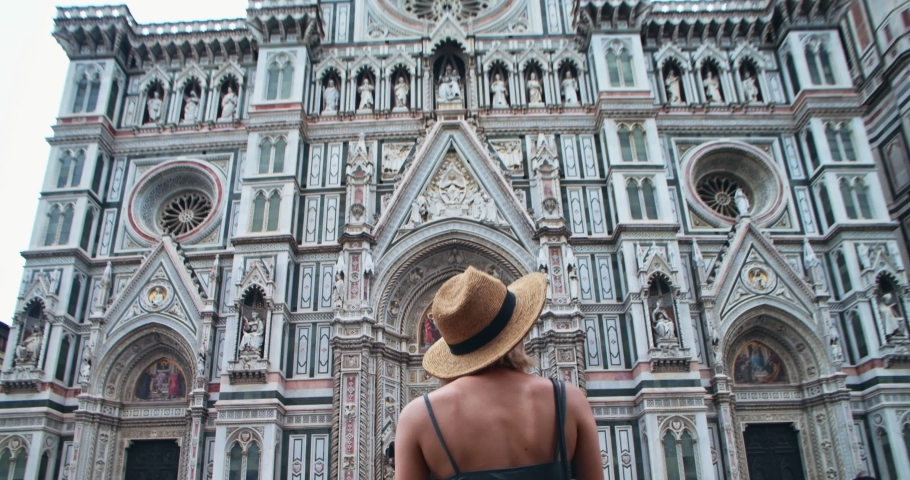 Florence, Italy. Back view of delighted young woman admiring glorious facade of Duomo di Firenze cathedral. Pretty girl tourist looking on city map exploring landmarks in famous Piazza del Duomo. | Shutterstock HD Video #1034343143