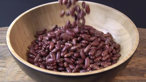 Dried red beans falling into a wooden bowl. Wooden background. Closeup. Food video. Uncooked beans Raw cereal falling into beautiful dishes Macro slow motion.