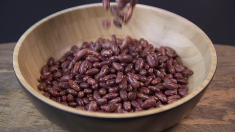 Red beans falling into a wooden bowl. Wooden background. Closeup. Food video. Uncooked beans Raw cereal falling into beautiful dishes Macro.