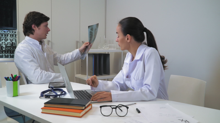 Doctor holding x-ray dictates diagnosis and conclusion for medical records. Woman nurse or assistant typing on computer. Colleagues sitting at the working place in clinic. | Shutterstock HD Video #1034410313