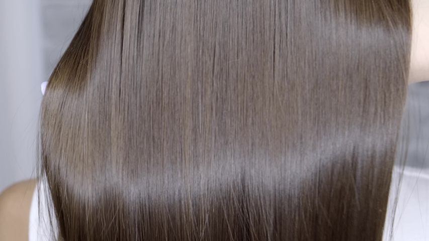 Result after lamination and hair straightening in a beauty salon for a girl with brown hair. hair care concept.   Shutterstock HD Video #1034425973