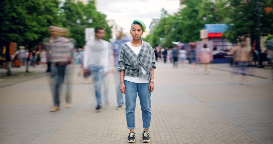 Time lapse of Asian teenage hipster standing in city center in busy street looking at camera wearing trendy clothes while crowds of people are walking by. | Shutterstock HD Video #1034434733