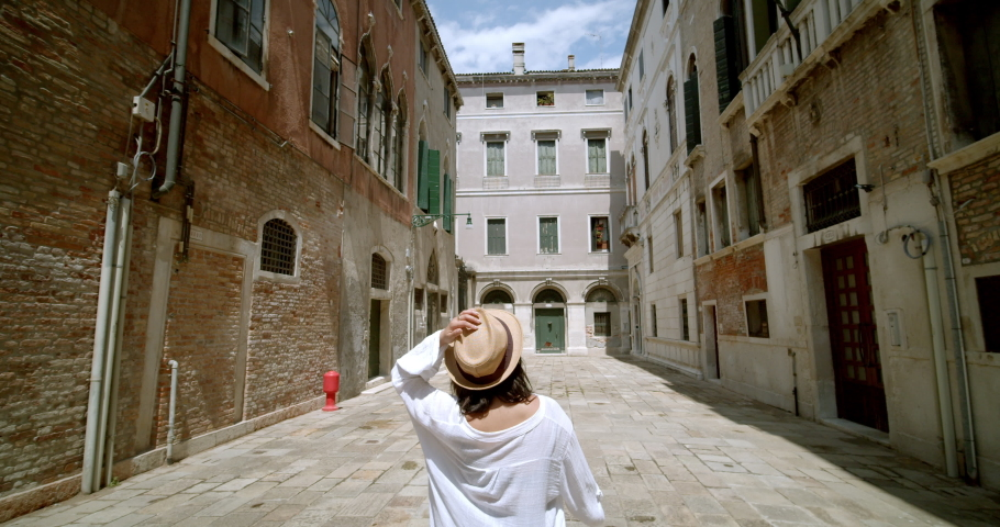 Female traveller looking around her as she enjoys one of the many beautiful historic streets in Venice Italy | Shutterstock HD Video #1034464013
