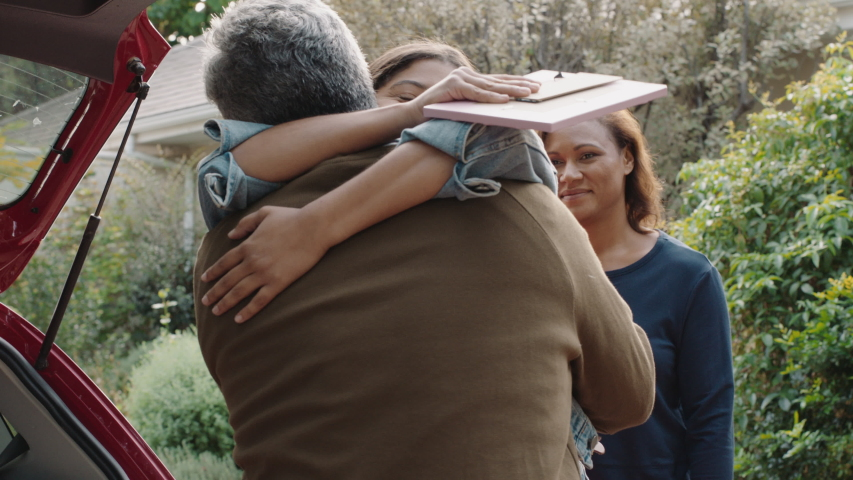 Young girl moving out of house leaving for college packing luggage in car hugging parents goodbye mother and father embracing daughter farewell 4k footage