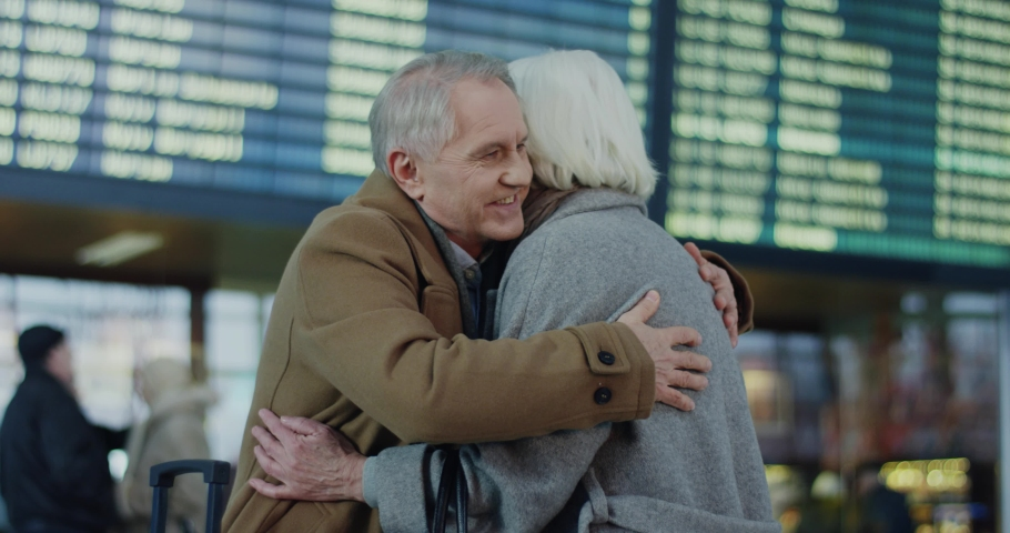 Caucasian old happy couple meeting and hugging at the airport terminal after one of them arrival. Indoor. | Shutterstock HD Video #1034506583