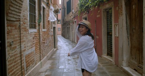 Attractive young traveller wearing fedora runs through a small street in Venice Italy waving and calling you to come along with her on her journey