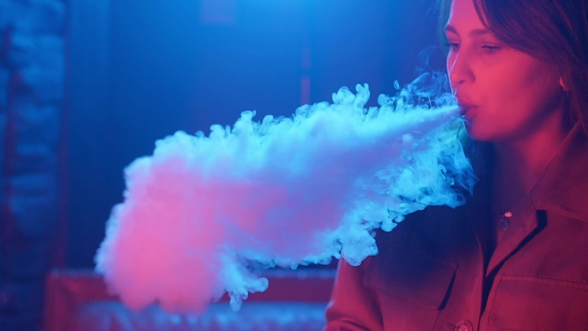 Young woman in neon red and blue smoke with vape or e-cigarettes #1034541713