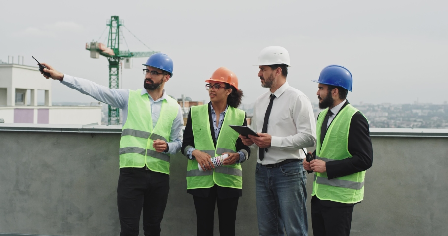 A group of multiethnic workers at construction site engineer architects and foreman analyzing the plan of construction site using a tablet and wearing safety helmets #1034626343