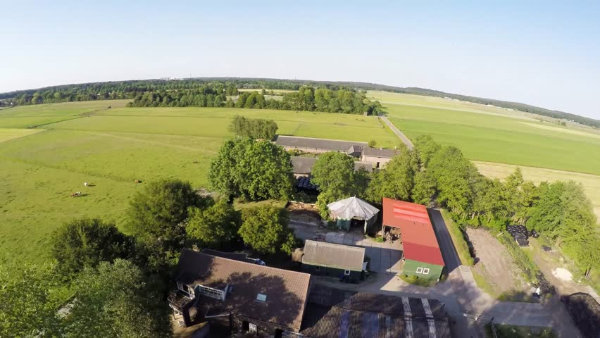 Drone aerial flying over a farm showing the tree line around the small farm and also showing the different barns and farmers buildings for storing agricultural equipments and hay for the animals 4k | Shutterstock HD Video #10346681