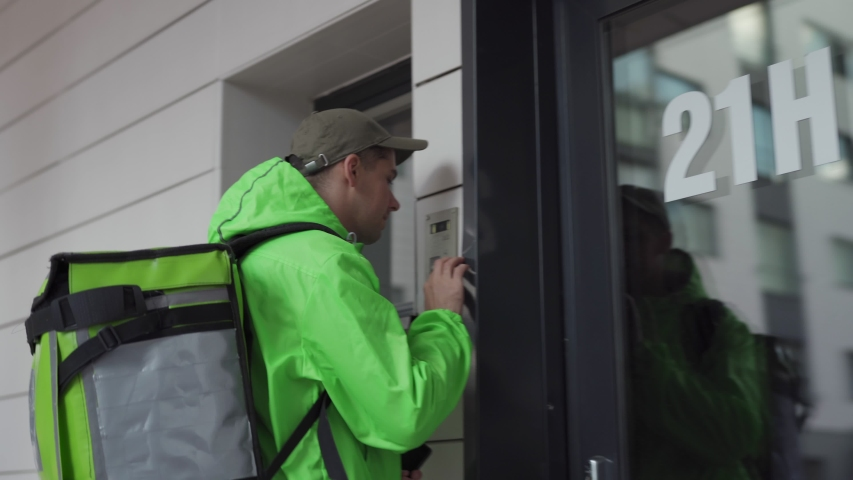Tilt up follow shot of young male food courier walking down street with thermal backpack delivering food. Man coming to building door, calling doorbell and entering house, cellphone in his hand | Shutterstock HD Video #1034735183