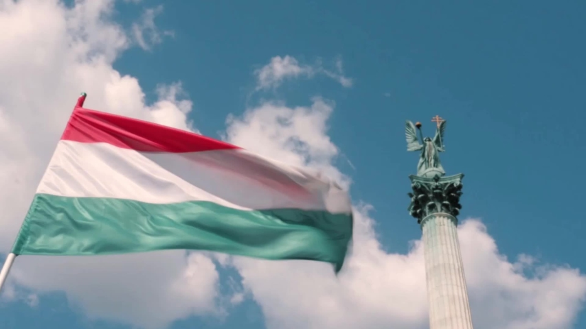 Flag of Hungary swaying in the wind on the heroes square in Budapest dedicated to the Millennium of the Hungarians homeland | Shutterstock HD Video #1034790533