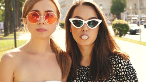 Portrait of two young beautiful smiling hipster girls in trendy summer clothes.Carefree women posing on street background. Positive models having fun in sunglasses and blowing bubble with chewing gum