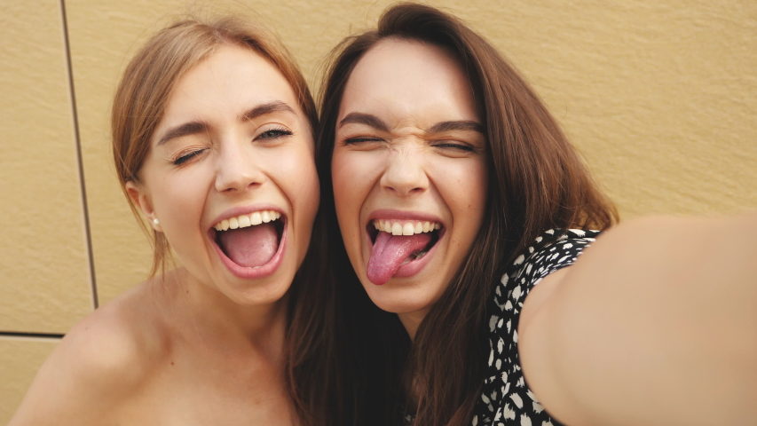 Two young smiling hipster women in summer clothes.Girls taking selfie self portrait photos on smartphone.Models posing in the street near yellow wall.Female shows tongue, peace sign and make duck face | Shutterstock HD Video #1034852573
