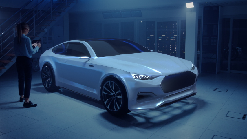 Female Automotive Engineer Uses Digital Tablet with Augmented Reality for Car Design Improvement. 3D Graphics Visualization Shows Fully Developed Vehicle Prototype With Turned On Headslights | Shutterstock HD Video #1034861843