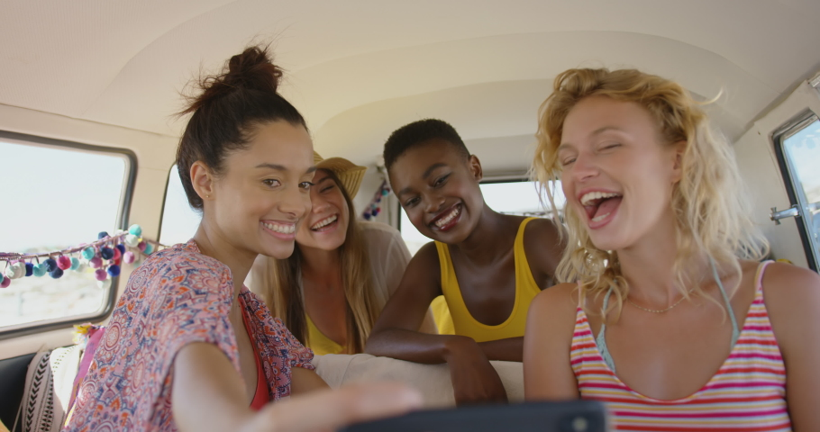 Close up of four multi-ethnic young adult female friends taking selfies with a smartphone and looking at them, sitting in the back of a camper van parked at a beach. Summer Road Trip in Camper Van to | Shutterstock HD Video #1034870153