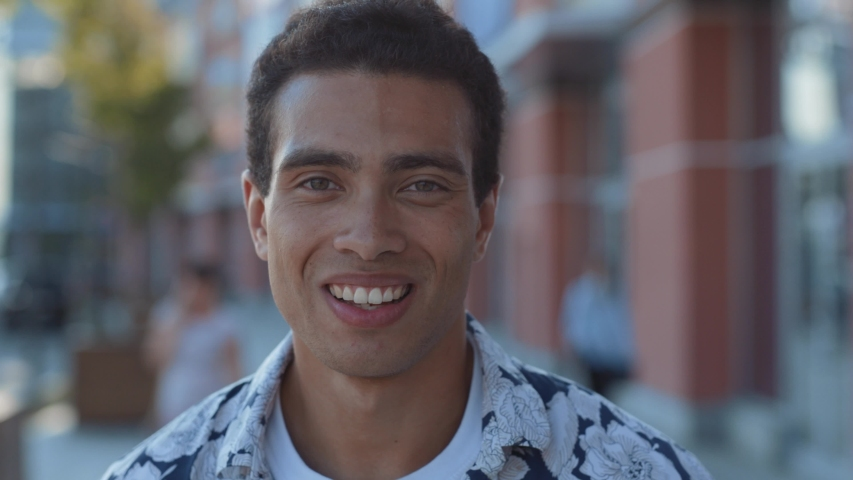face portrait of attractive mixed race young man in stylish look smiling of joy walking in the beautiful city center on summer sunny day. #1034878673