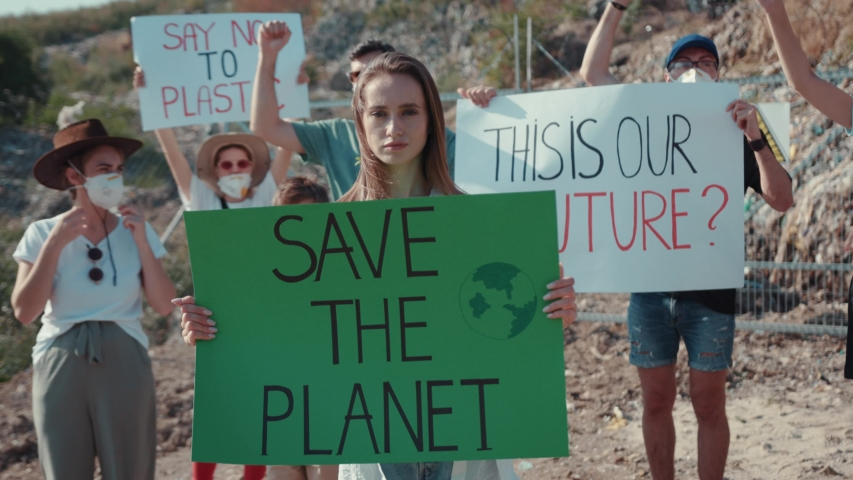 Young activists in action against pollution stay at landfill site. Focus on young woman holding climate strike poster at protest strike. Save the Planet. #1034925833