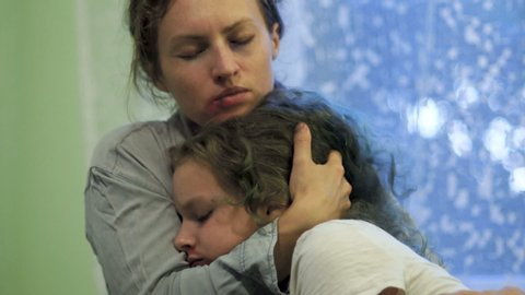 Beaten mother and daughter cry hugging. Indoor portrait, stop violence, eastern europe