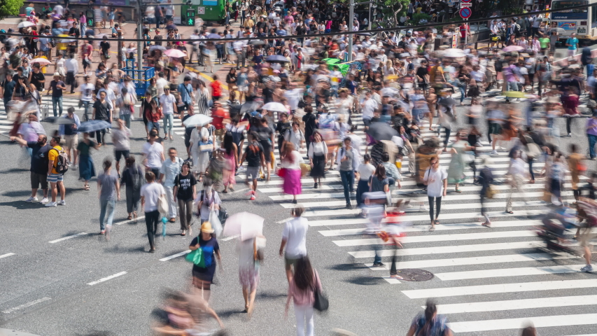 4K Timelapse high angle view wide shot of crowded pedestrian man and woman tourist walking crossing the street crosswalk with driving cars on the road cityscape in summer at Shibuya, Tokyo City, Japan