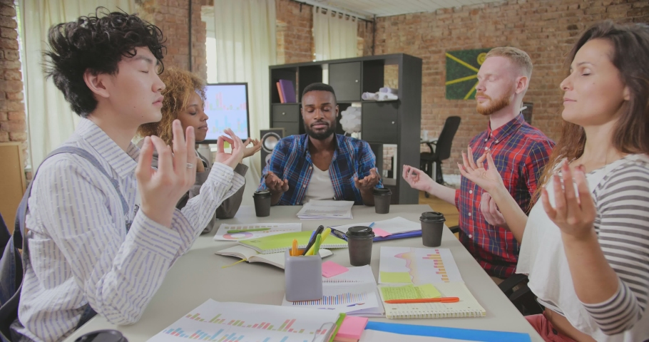 Mindful multiracial colleagues meditate at workplace feeling zen, enjoying stress relief. Corporate meditation concept | Shutterstock HD Video #1035021713