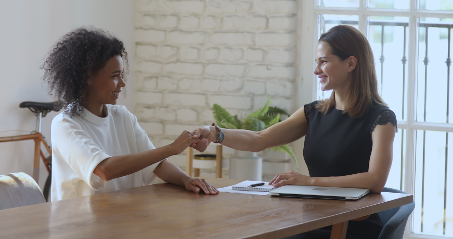 Happy female hr bank manager insurer talk handshake job applicant get hired at interview, happy caucasian businesswoman broker shake hand of african client, business agreement and recruitment concept