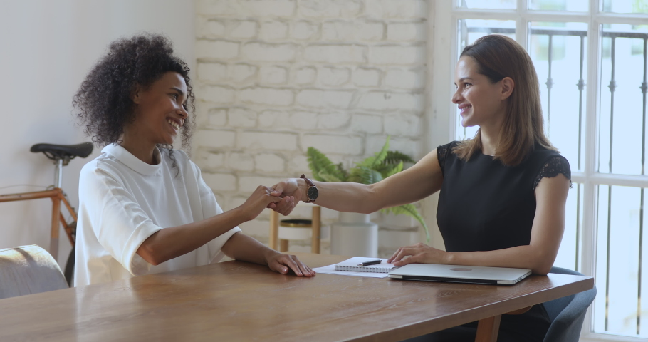 Happy female hr bank manager insurer talk handshake job applicant get hired at interview, happy caucasian businesswoman broker shake hand of african client, business agreement and recruitment concept | Shutterstock HD Video #1035023903