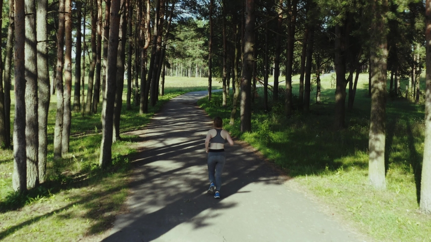Young attractive girl running in city park. Woman running in wood aerial back view. 4K, tracking shot. | Shutterstock HD Video #1035029783