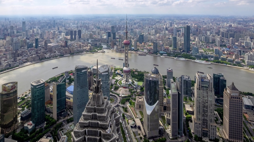 Time lapse of shanghai bund, modern city in cloudy afternoon, aerial view of bund skyline, ships sailing on huangpu river and busy traffic on road, 4k Version, b roll shot.