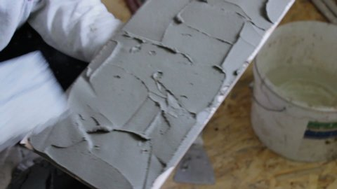 glue With Spatula put on a ceramic tile,hand with a spatula impose a solution of glue on the ceramic tile