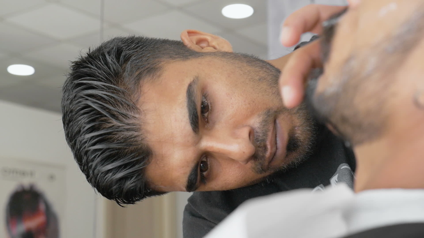 Barbershop. Hairstylist trimming consumer beard with a straight razor. Stylish barber shaves client in an old-fashion manner. Man getting a shave with a blade in a traditional barbershop. | Shutterstock HD Video #1035065333