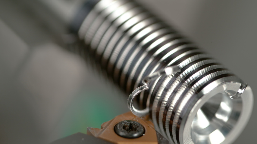 SLOW MOTION, MACRO, DOF: CNC machine slowly threading a small metal workpiece into a shiny screw. Sharp cutter carving deep grooves into a silver colored workpiece during thread cutting process. | Shutterstock HD Video #1035089993