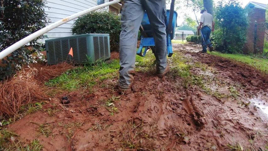A man pushes a wheelbarrow across muddy ground on a job site | Shutterstock HD Video #1035094433