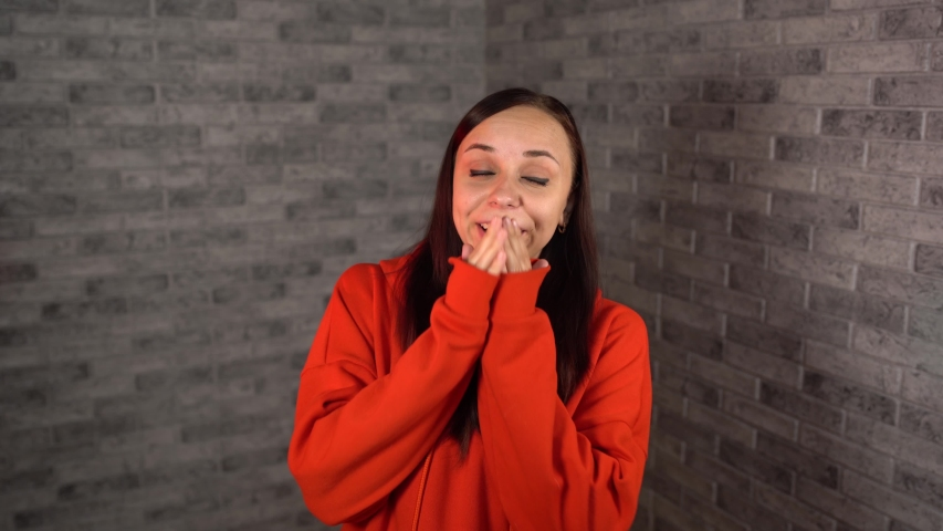 A beautiful young woman in a red hoodie yawns from fatigue on a brick background.   Shutterstock HD Video #1035177893