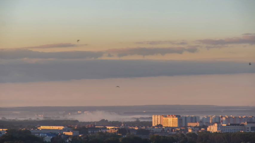 Timelapse of an urban landscape in foggy rosy morning. Residental area in small city outskirts during summer sunrise. Aerial view of the beautiful morning panorama with green trees and fog | Shutterstock HD Video #1035178163