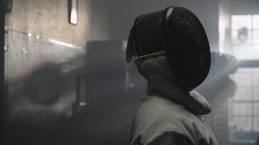 Portrait of an older man fencer taking off his mask and looking at the camera | Shutterstock HD Video #1035247493