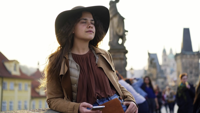 Pretty woman in hat standing on charles bridge in sunny day. Close-up portrait girl in backlit communicate by phone while walking on street historical centre of Prague at background famouse sights | Shutterstock HD Video #1035310913