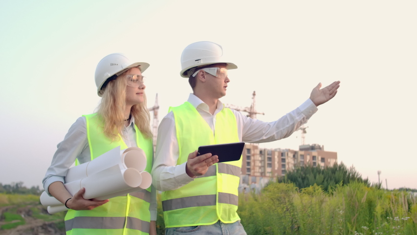 Two industrial engineer wear safety helmet and holding tablet engineering working and talking with drawings inspection. On building outside. Engineering tools | Shutterstock HD Video #1035355313