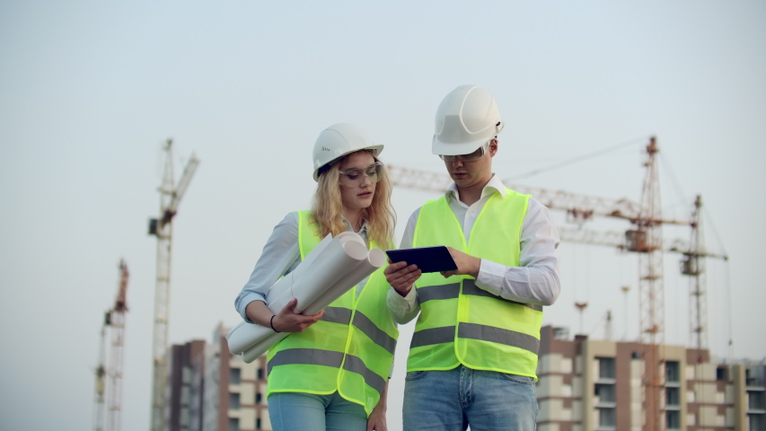 Adult engineer man and architect woman uses a tablet in operation. Writes a message or checks a drawing. Against background is building. | Shutterstock HD Video #1035360353