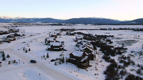 Aerial Forward: A Minivan Drives Through a Snow Covered Neighborhood in Tabernash with View of Mountains