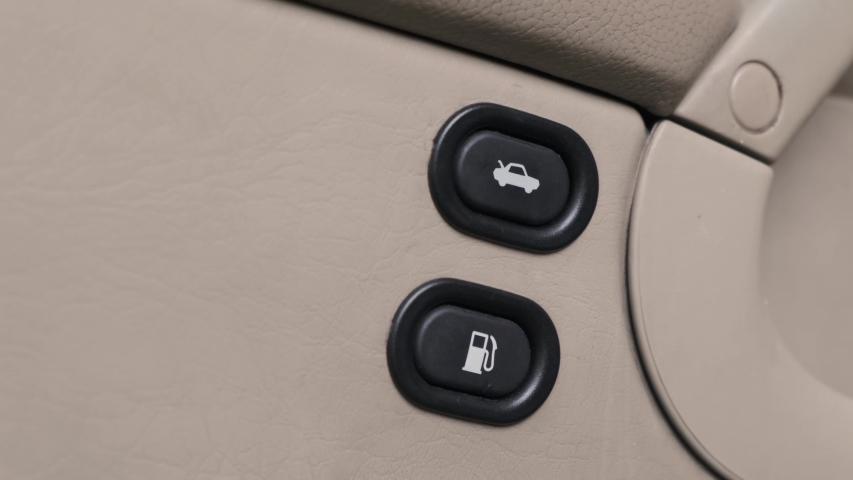Person hand press button opens trunk on the car door. | Shutterstock HD Video #1035389453