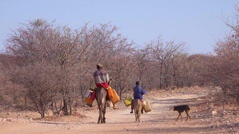 DAMARALAND, NAMIBIA - CIRCA 2018 - Two Himba men ride donkeys along a dusty road in Africa, Damaraland, Namibia bringing water to remote villages.